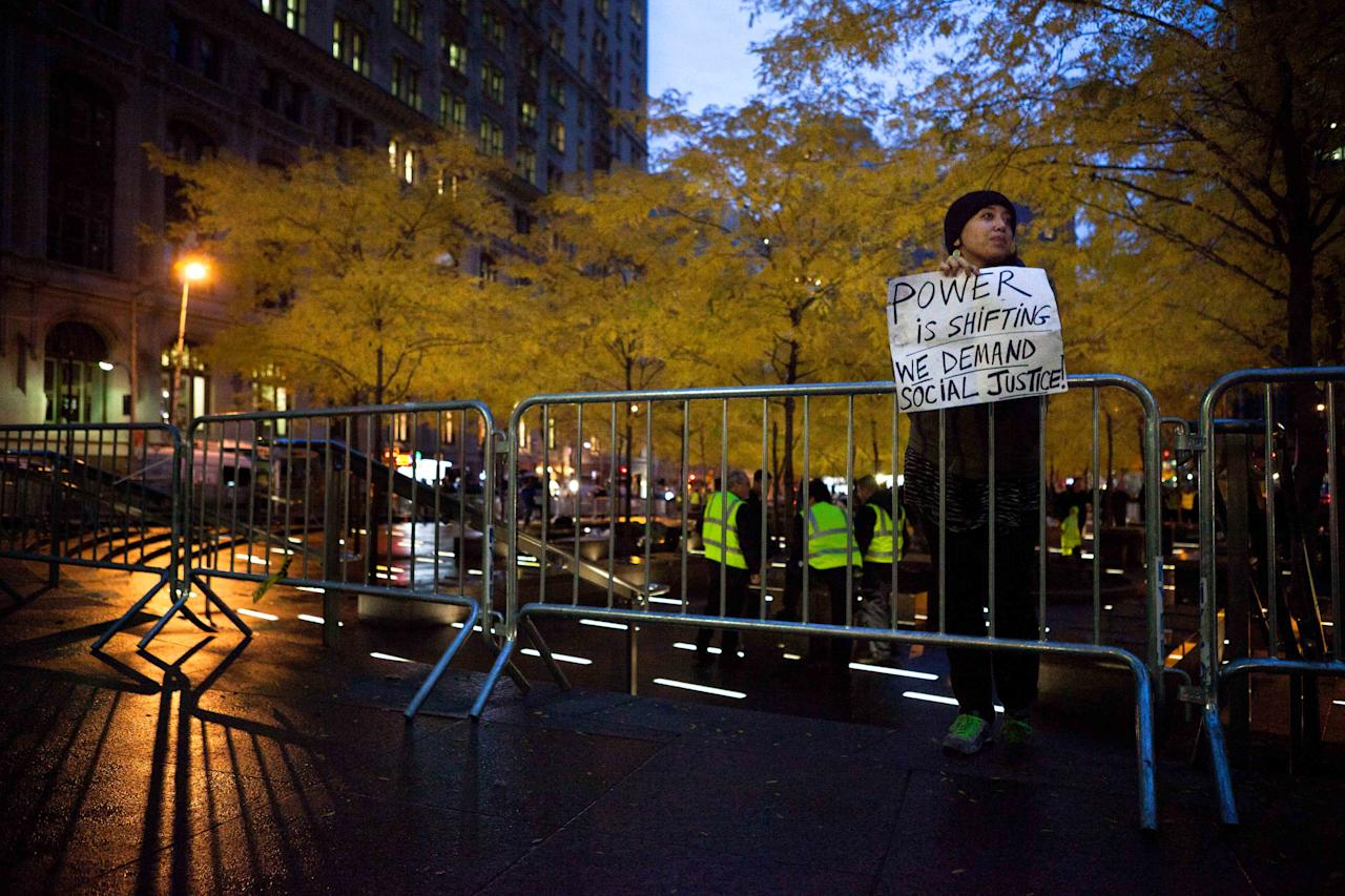 A solitary Occupy Wall Street protestor holds a sign outside a nearly empty Zuccotti Park during the early morning hours, Wednesday, Nov. 16, 2011, in New York. Crackdowns against the Occupy Wall Street encampments across the country reached the epicenter of the movement Tuesday, when police rousted protesters from the park and a judge ruled that their free speech rights do not extend to pitching a tent and setting up camp for months at a time. (AP Photo/John Minchillo)