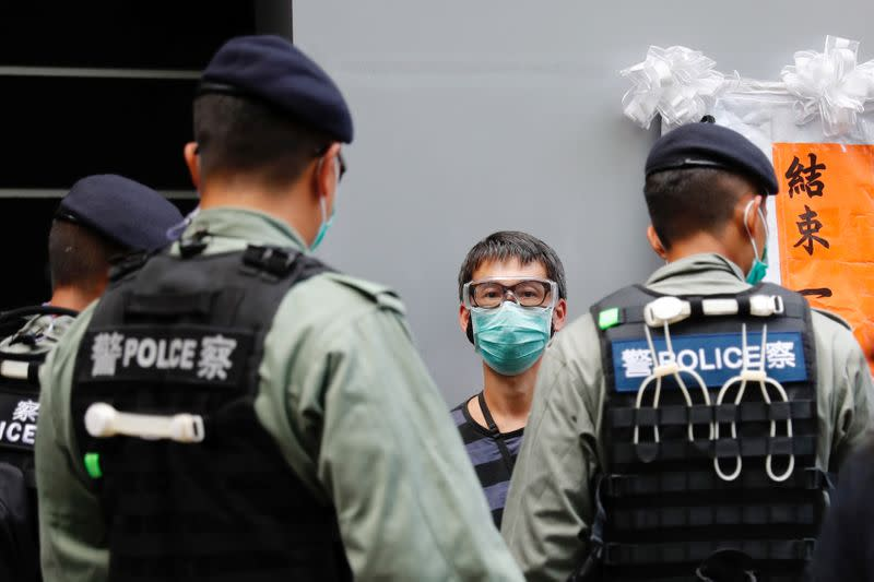 Police search a pro-democracy protester during a demonstration on the anniversary of Hong Kong's handover to China