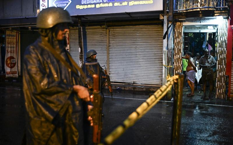 Sri Lankan soldiers stand guard under the rain at St. Anthony's Shrine in Colombo - AFP