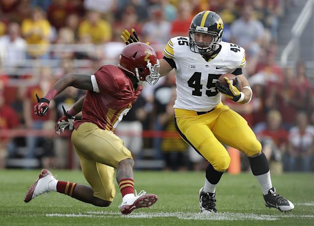 Iowa fullback Mark Weisman, right, runs from Iowa State defensive back Jansen Watson, left, during the first half of an NCAA college football game, Saturday, Sept. 14, 2013, in Ames, Iowa. (AP Photo/Charlie Neibergall)