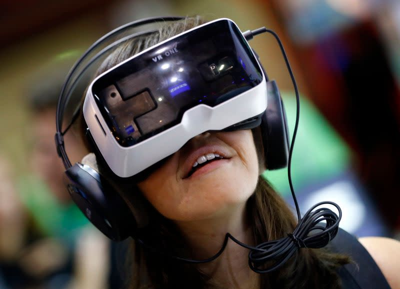 """A woman tests a virtual reality headset """"VR One"""" developed by a German manufacturer Zeiss at the Gamescom 2015 fair in Cologne"""