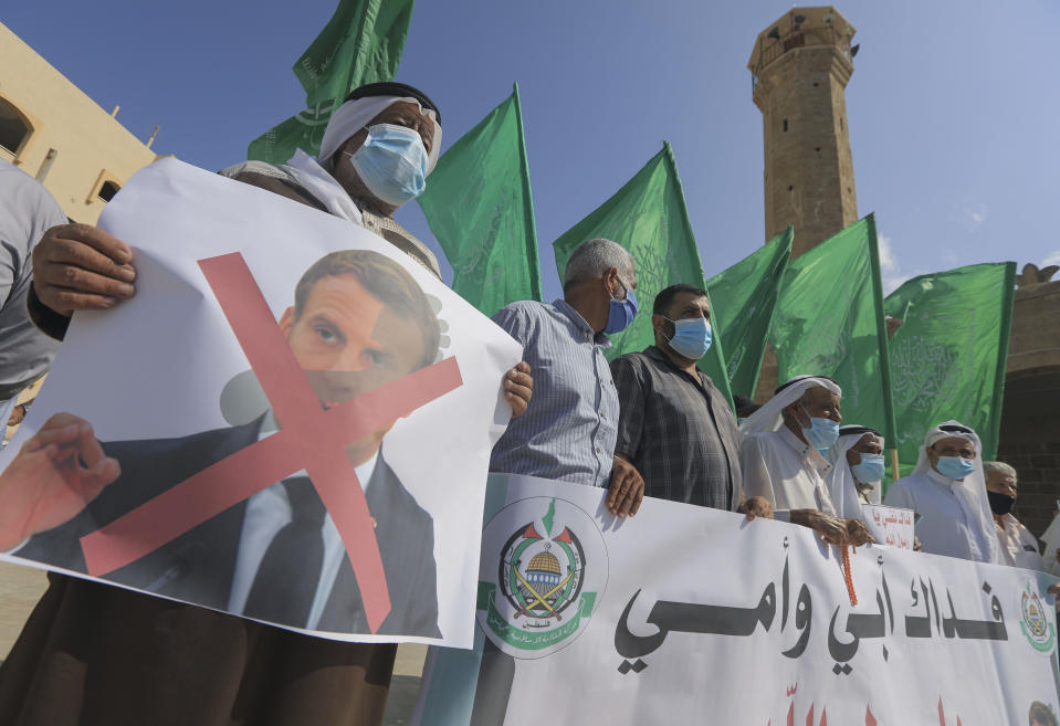 Palestinian demonstrators lift flags and placards during a rally to protest comments of French President Emmanuel Macron over Prophet Mohammed cartoons, in Deir al-Balah in the central Gaza Strip, on October 25, 2020. (Photo by MAHMUD HAMS / AFP) (Photo by MAHMUD HAMS/AFP via Getty Images)