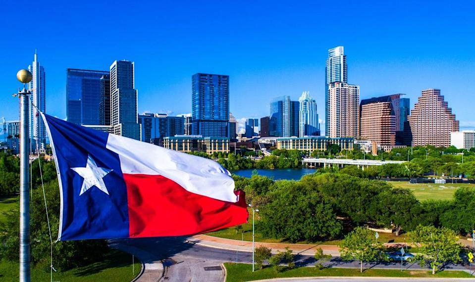 Lone Star flag flying in front of the Austin, Texas, skyline