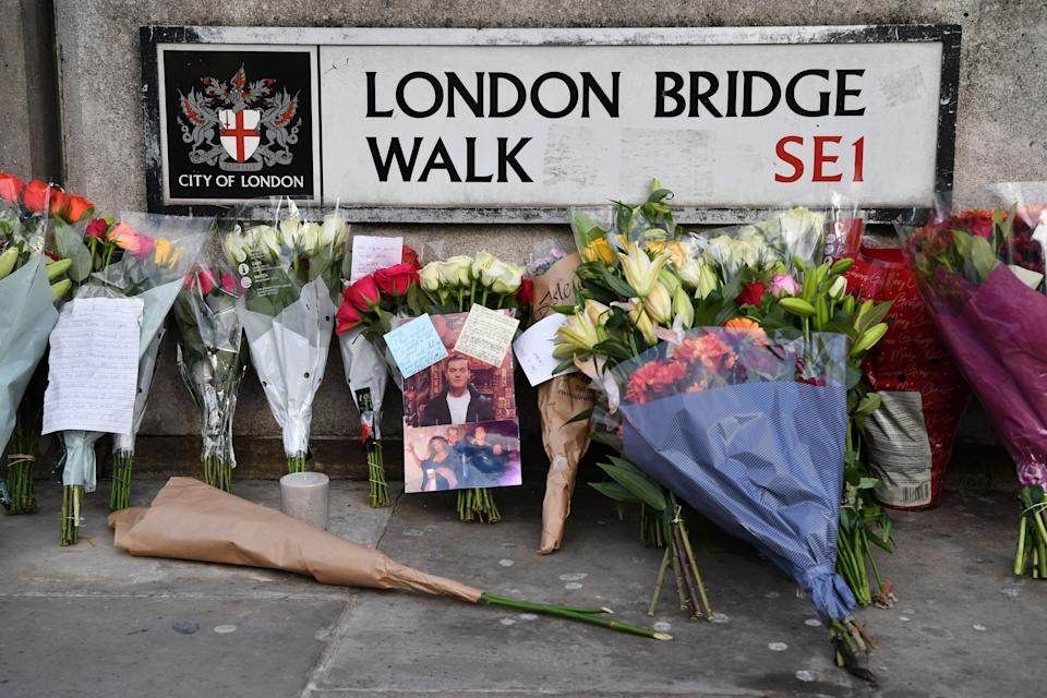 Floral tributes and photographs of the first victim to be named, Jack Merritt, are pictured close to London Bridge in the City of London, on December 1, 2019, following the November 29 deadly terror incident. - Britain's Boris Johnson said on December 1 the security services were stepping up monitoring of convicted terrorists released early from prison, as the London Bridge attack became embroiled in the election campaign. (Photo by Ben STANSALL / AFP) (Photo by BEN STANSALL/AFP via Getty Images)