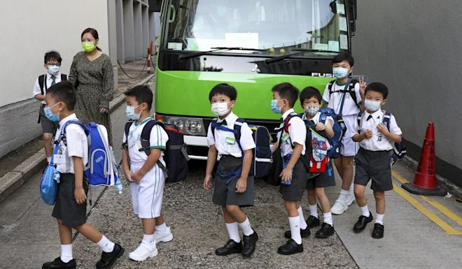 Children arrive for their first day back in the classroom at their school in Wan Chai. Photo: Nora Tam