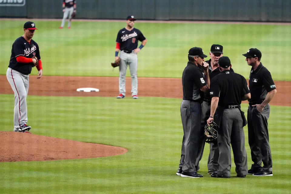 The umpiring crew meets before ejecting Washington Nationals pitcher Sean Nolin, left, after he hit Atlanta Braves' Freddie Freeman with aa pitch during the first inning of a baseball game Wednesday, Sept. 8, 2021, in Atlanta. (AP Photo/John Bazemore)