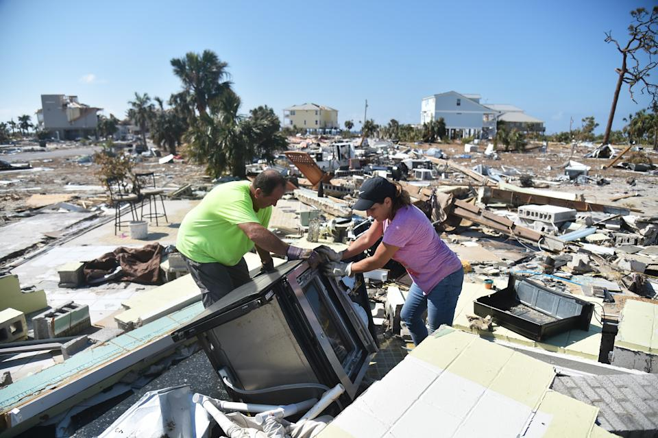 Frank and his sister try to recover belongings from their house destroyed by Hurricane Michael in Mexico Beach, Florida. (Photo: HECTOR RETAMAL/AFP via Getty Images)