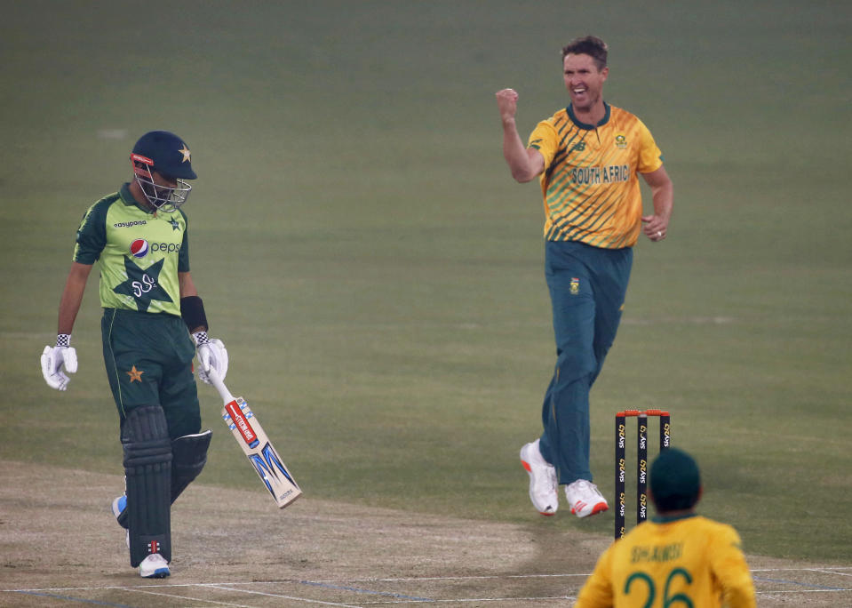 Pakistan's Babar Azam, left, walks back to pavilion while South Africa's Dwaine Pretorius celebrates his dismissal during the 2nd Twenty20 cricket match between Pakistan and South Africa at the Gaddafi Stadium, in Lahore, Pakistan, Saturday, Feb. 13, 2021. (AP Photo/K.M. Chaudary)
