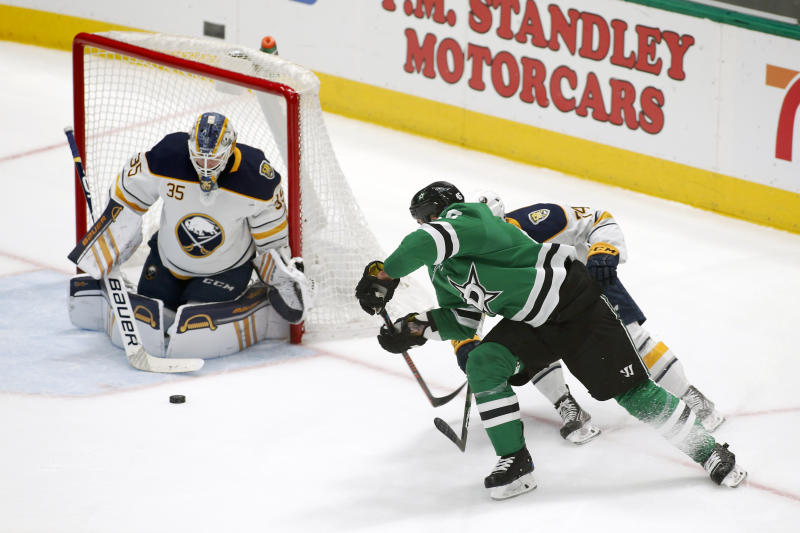 Buffalo Sabres goaltender Linus Ullmark, left, makes the save of the shot by Dallas Stars defenseman Roman Polak, right, as center Rasmus Asplund, obscured, defends during the second period of an NHL hockey game in Dallas, Thursday, Jan. 16, 2020. (AP Photo/Ray Carlin)