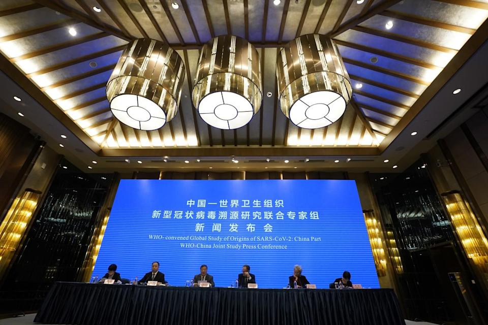 People in suits sit at a table in front of a large blue screen that has Chinese characters English words.