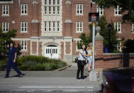 FILE- In this Sept. 18, 2015 file photo, a University of Connecticut student pushes a button at a crosswalk outside one of the student dormitories, in Storrs, Conn. On Friday, Nov. 13, 2020, the University of Connecticut announced that it has placed all dormitories at its main campus under quarantine because of rising coronavirus infections. (AP Photo/Jessica Hill, File)