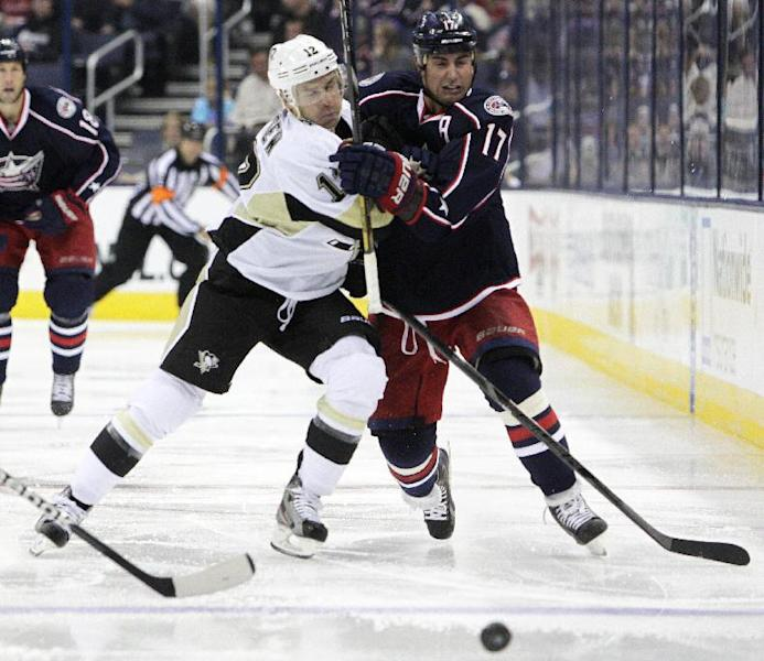 Pittsburgh Penguins' Chuck Kobasew, left, and Columbus Blue Jackets' Brandon Dubinsky chase the loose puck during the second period of an NHL preseason hockey game, Sunday, Sept. 15, 2013, in Columbus, Ohio. (AP Photo/Jay LaPrete)