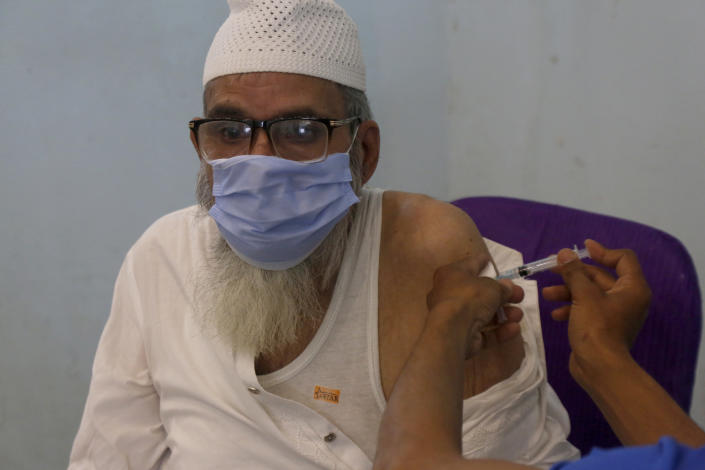A man receives the second shot of the AstraZeneca COVID-19 vaccine from a health worker at a vaccination center in Lahore, Pakistan, Sunday, May 16, 2021. (AP Photo/K.M. Chuadary)
