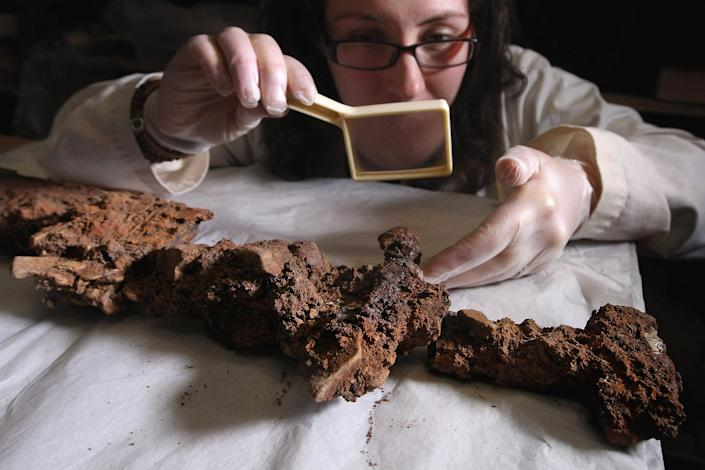 Dr Hannah Cobb from The University of Manchester looks at a viking sword during a viewing at CFA Archaeology of artefacts discovered from the first fully intact Viking boat burial site on October 18, 2011 in Edinburgh, Scotland. The 5 meter long grave uncovered on the Ardnamurchan peninsula, contained the remains of a high status Viking, who was buried with an axe, a sword with decorated hilt, a spear, shield boss and bronze ring pin. (Photo by Jeff J Mitchell/Getty Images)