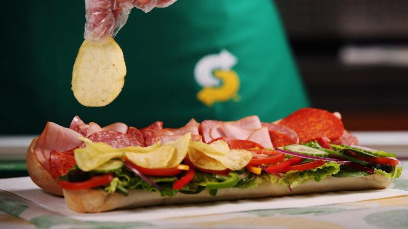 Subway employee sprinkling chips over sandwich