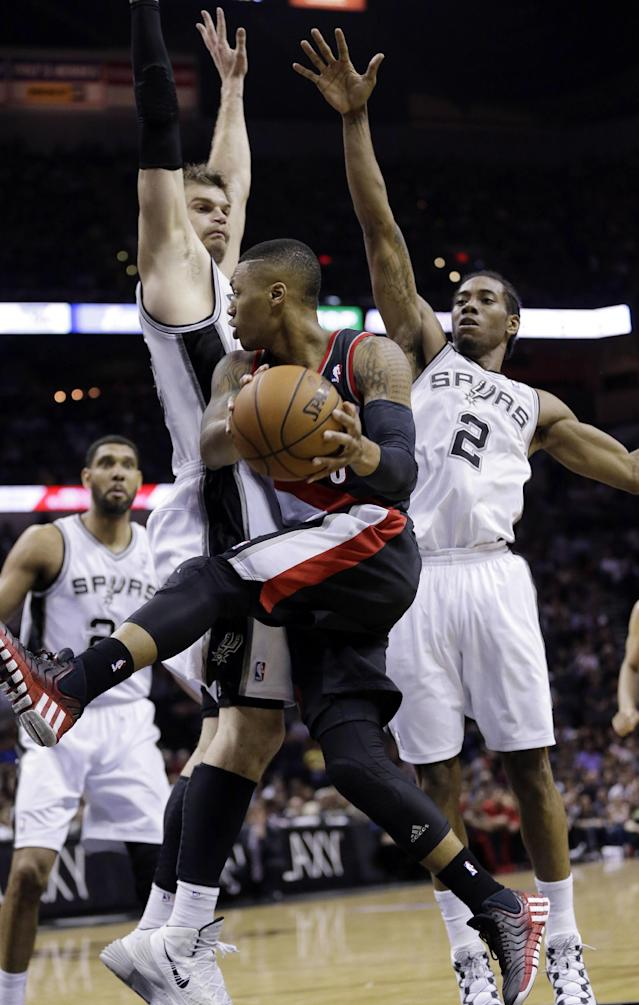 Portland Trail Blazers' Damian Lillard, center, drives around San Antonio Spurs' Tiago Splitter, of Brazil, and Kawhi Leonard (2) during the second half of Game 1 of a Western Conference semifinal NBA basketball playoff series, Tuesday, May 6, 2014, in San Antonio. (AP Photo/Eric Gay)