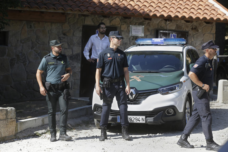 Police wait near a woodland area in Cercedilla, just outside of Madrid, Spain, Tuesday, Sept. 3, 2019. A search squad of hundreds is combing a mountainous area outside Madrid 11 days after former alpine ski racer and Olympic medalist Blanca Fernandez Ochoa went missing.(AP Photo/Paul White)