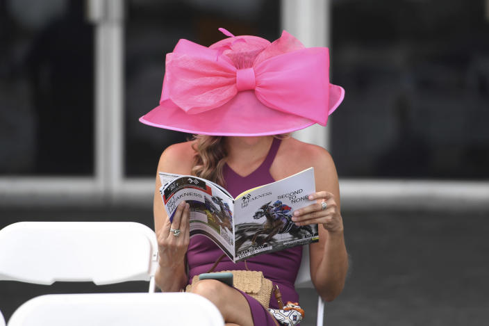 A woman reads a program ahead of the Preakness Stakes horse race at Pimlico Race Course, Saturday, May 15, 2021, in Baltimore. (AP Photo/Will Newton)