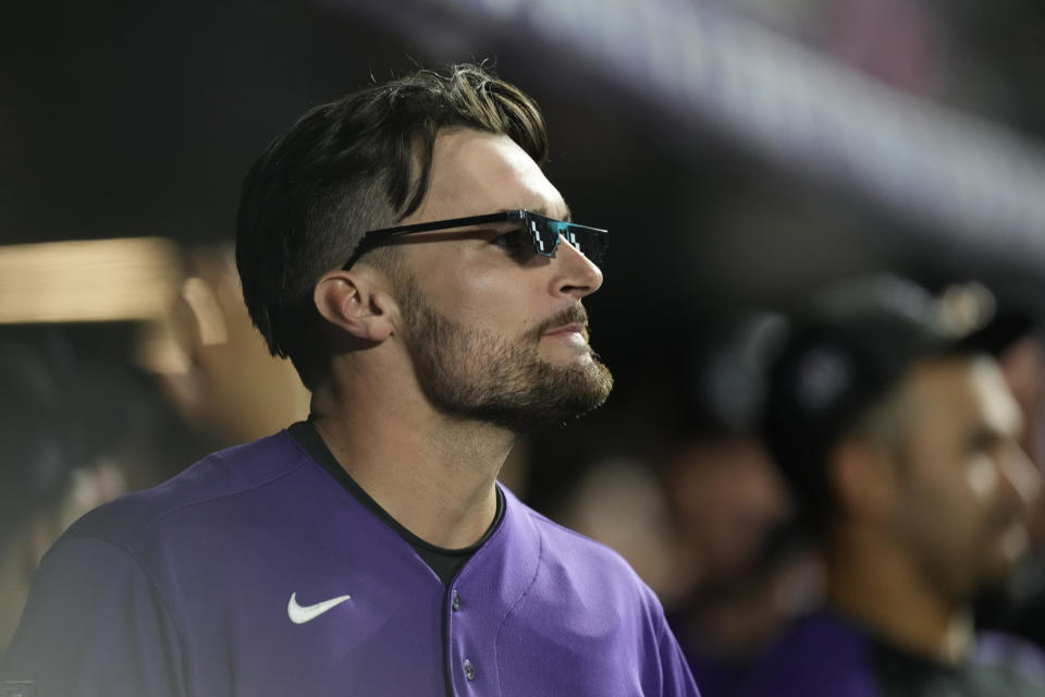 Colorado Rockies' Sam Hilliard dons a pair of home run shades as he returns to the dugout after hitting a two-run home run off Los Angeles Dodgers relief pitcher Alex Vesia in the seventh inning of a baseball game Wednesday, Sept. 22, 2021, in Denver. (AP Photo/David Zalubowski)