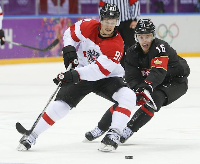 Austria forward Oliver Setzinger, left, and Canada forward Jonathan Toews vie for the puck in the second period of a men's ice hockey game at the 2014 Winter Olympics, Friday, Feb. 14, 2014, in Sochi, Russia. (AP Photo/Mark Humphrey)