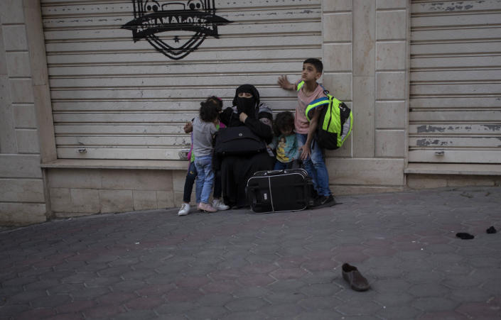 A Palestinian family sit on the street side after they were evacuated from a building following Israeli airstrikes on Gaza City, Wednesday, May 12, 2021. Rockets streamed out of Gaza and Israel pounded the territory with airstrikes early Wednesday as the most severe outbreak of violence since the 2014 war took on many of the hallmarks of that devastating 50-day conflict, with no endgame in sight. (AP Photo/Khalil Hamra)