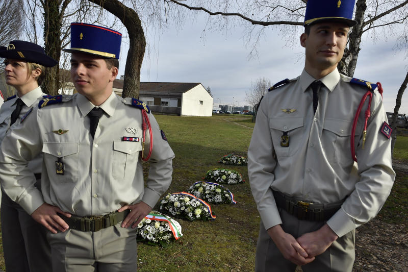 French soldiers stand next wreaths of flowers as they prepare for a ceremony with French President Emmanuel Macron to pay tribute to French soldiers who died in Mali helicopter crash, Monday Jan.13, 2020 in Pau, southwestern France. France is preparing its military to better target Islamic extremists in a West African region that has seen a surge of deadly violence. (AP Photo/Alvaro Barrientos, Pool)