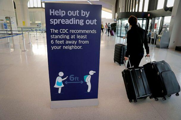PHOTO: Travelers pass a social-distancing sign as they arrive to check in for flights ahead of the Thanksgiving holiday at Newark International Airport in Newark, N.J., Nov. 25, 2020. (Mike Segar/Reuters)