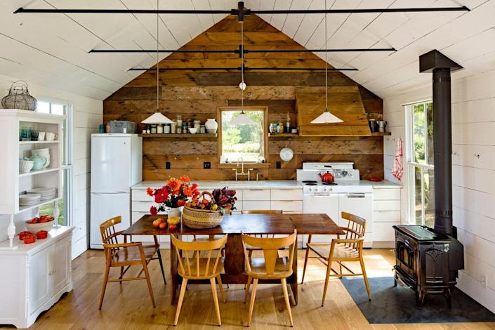 On one side of the tiny house, the great room is home to the dining room and kitchen, which were furnished with vintage pieces of furniture. The walls are covered in wood cladding reclaimed from a barn on the property.