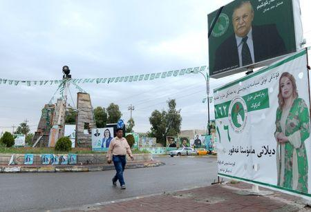 A man walks past a campaign poster ahead of the parliamentary election in Kirkuk