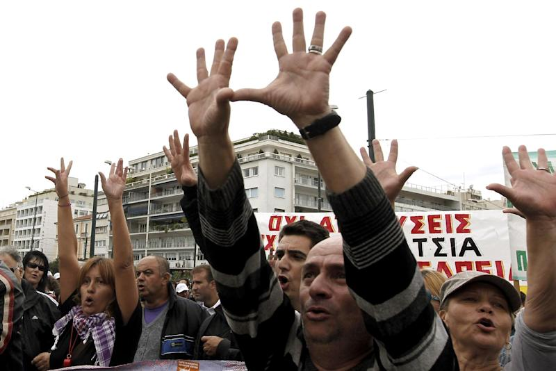 Civil servants gesture towards the Greek parliament during a protest in Athens, on Tuesday, Oct. 11, 2011. Greece's international debt inspectors have completed their review of the government's reforms, saying Tuesday that if their conclusions are adopted by the eurozone and IMF, Athens is likely to receive the next batch of its bailout loans in early November.  (AP Photo/Petros Giannakouris)