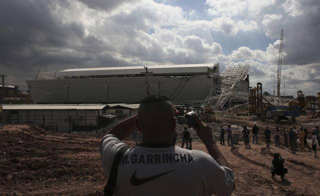 """A man records the crane that collapsed on the site of the Arena Sao Paulo stadium, known as """"Itaquerao"""", which will host the opening soccer match of the 2014 World Cup, in Sao Paulo"""