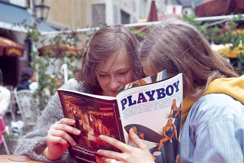 Hamelin, Lower Saxony, 1979. Two young women read together an article in a well-known men's magazine in a pedestrian area.
