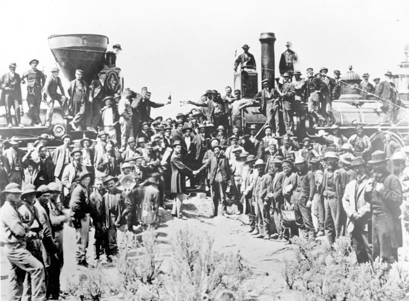 FILE - In this May 10, 1869, file photo, provided by the Union Pacific, railroad officials and employees celebrate the completion of the first railroad transcontinental link in Promontory, Utah. The completion of the Transcontinental Railroad was a pivotal moment in the United States, ushering in a period of progress and expansion nationwide. The Union Pacific's Locomotive No. 119, right, and Central Pacific's Jupiter edged forward over the golden spike that marked the joining of the nation by rail. (Andrew Russell/Union Pacific via AP, File)