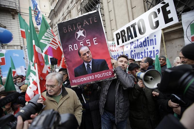 "A supporter displays a poster depicting Italian Former Premier Silvio Berlusconi on the backdrop of former Italian terrorist group Brigate Rosse (Red Brigates) and reading in Italian ""Political prisoner"", while he waits for Berlusconi's speech at a rally organized outside of his Rome residence, Wednesday, Nov. 27, 2013. The Italian Senate has begun debating whether to kick Silvio Berlusconi out of Parliament following his tax fraud conviction. The vote is scheduled later in the day and most analysts expect he will lose his seat. Berlusconi fans massed in front of Berlusconi's Rome palazzo for a planned rally that analysts say is essentially the start of Italy's next electoral campaign. (AP Photo/Andrew Medichini)"