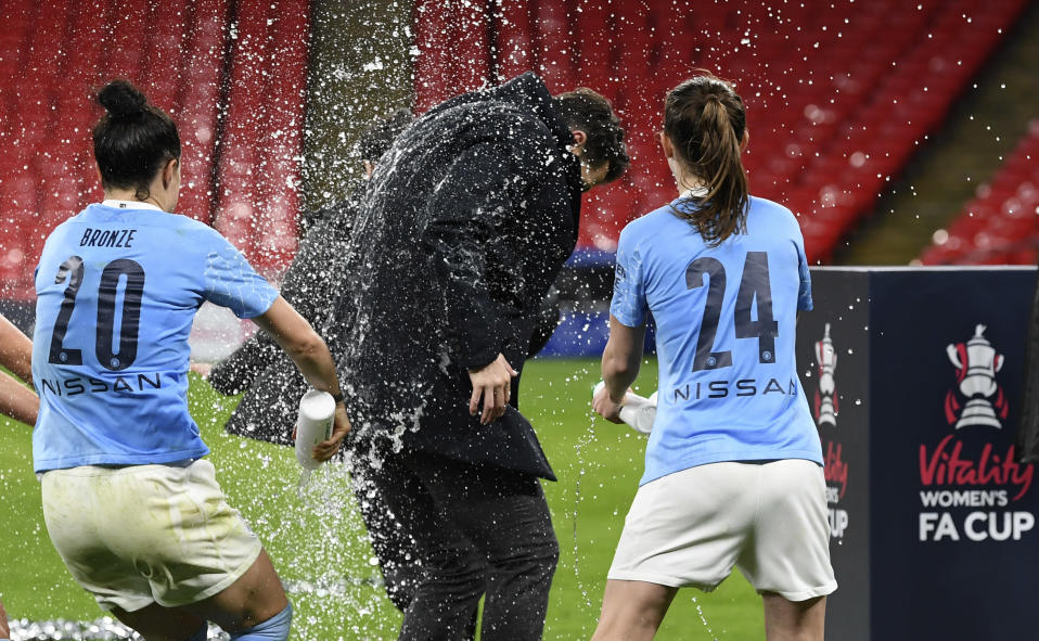 Manchester City's Lucy Bronze, left, and Keira Walsh, right, celebrate with Manchester City's manager Gareth Taylor, center, after winning the Women's FA Cup final soccer match between Everton and Manchester City at Wembley stadium in London, Sunday, Nov. 1, 2020. (Facundo Arrizabalaga/Pool via AP)