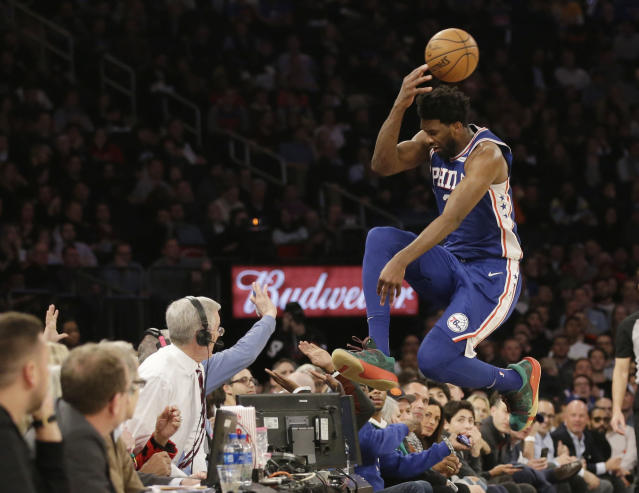 Joel Embiid leaps into the stands while chasing a loose ball during the second half against the New York Knicks on Wednesday. The 76ers won 126-111. (AP Photo/Frank Franklin II)
