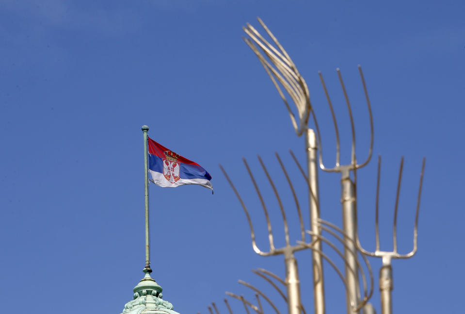 A Serbian flag waves on the Serbian Parliament building during a protest in front of the Serbian Parliament building in Belgrade, Serbia, Saturday, April 10, 2021. Environmental activists are protesting against worsening environmental situation in Serbia. (AP Photo/Darko Vojinovic)