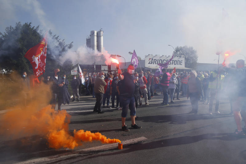 Bridgestone employees fire flares outside the tire factory of Bethune, northern France, Thursday, Sept.17, 2020. Workers protest over the Japan-based company's decision to close the plant and lay off all its nearly 900 workers. Bridgestone argues the factory is no longer competitive globally, but unions and French politicians accused the company of using the virus-driven economic crisis as a pretext for the closure and not investing in modernizing the plant instead. (AP Photo/Michel Spingler)