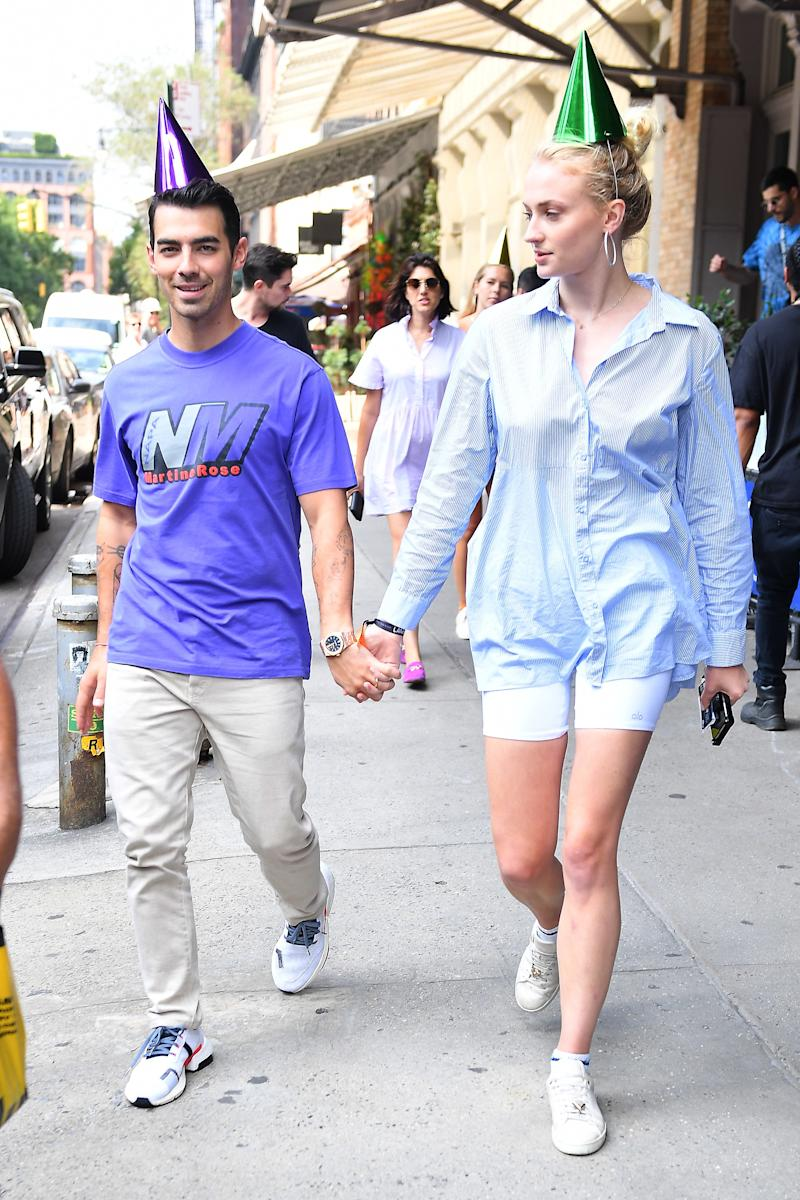 Joe Jonas and Sophie Turner walking through New York City in their party hats.