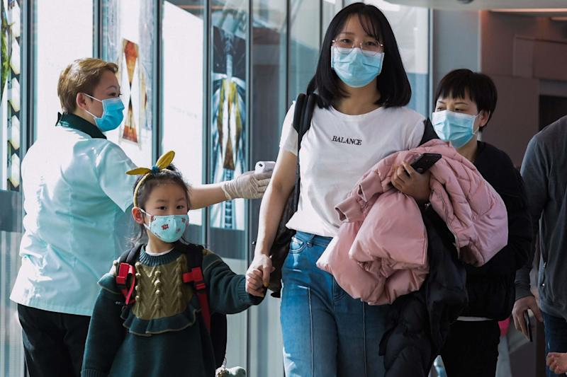 A health officer (L) screens arriving passengers from China in Singapore (AFP via Getty Images)