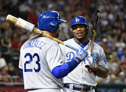 Yasiel Puig (R) talks with teammate Adrian Gonzalez during Monday's game vs. the D-backs. (Getty)