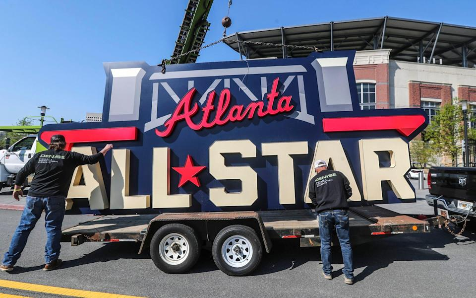 Workers remove an All-Star sign from Truist Park in Atlanta after Major League Baseball moved the showpiece game - AP