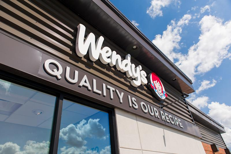 The exterior of a Wendy's restaurant against a blue sky.