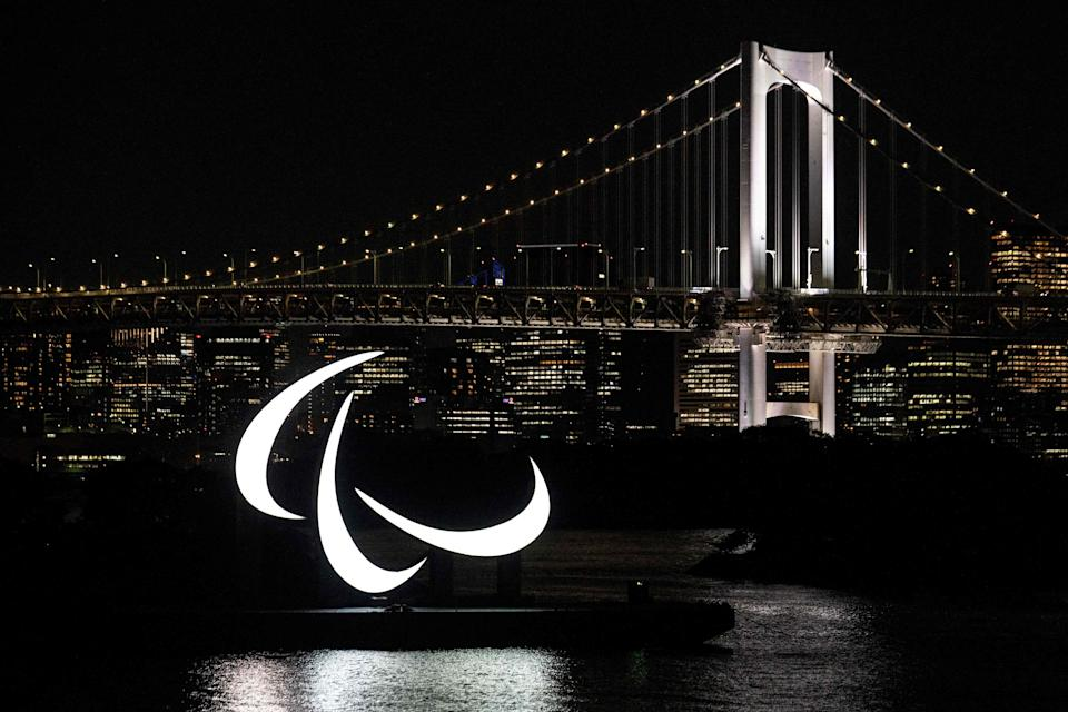 The Paralympics symbol is seen lit up at night with the Rainbow bridge in the background, on the Odaiba waterfront in Tokyo on August 23, 2021.