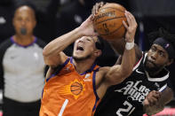 Phoenix Suns guard Devin Booker, left, is folded by Los Angeles Clippers guard Patrick Beverley as he tries to shoot during the first half in Game 3 of the NBA basketball Western Conference Finals Thursday, June 24, 2021, in Los Angeles. (AP Photo/Mark J. Terrill)