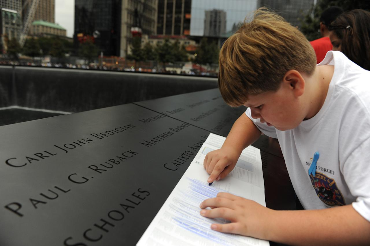 August Larsen, 9, makes a crayon rubbing of the engraving of the name of his father, Scott Larsen, on the wall of the south pool at the National September 11 Memorial in New York during a ceremony marking the 10th anniversary of the attacks on the World Trade Center Sunday, Sept. 11, 2011. Scott Larson, a firefighter at Ladder 15, never met his son, who was born just a few days after Scott's death in the terrorist attacks. (AP Photo/Aaron Showalter, Pool)