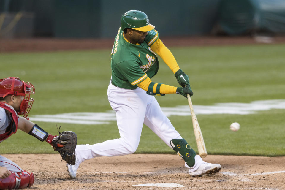 Oakland Athletics' Elvis Andrus, right, hits an RBI single in front of Los Angeles Angels catcher Max Stassi during the third inning of a baseball game in Oakland, Calif., Monday, June 14, 2021. (AP Photo/John Hefti)