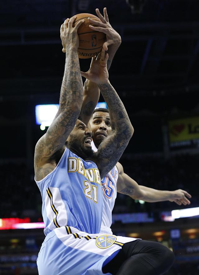 Oklahoma City Thunder guard Thabo Sefolosha (25) gets his hand on the ball as Denver Nuggets forward Wilson Chandler (21) goes up for a shot in the first quarter of an NBA basketball game in Oklahoma City, Monday, Nov. 18, 2013. (AP Photo/Sue Ogrocki)