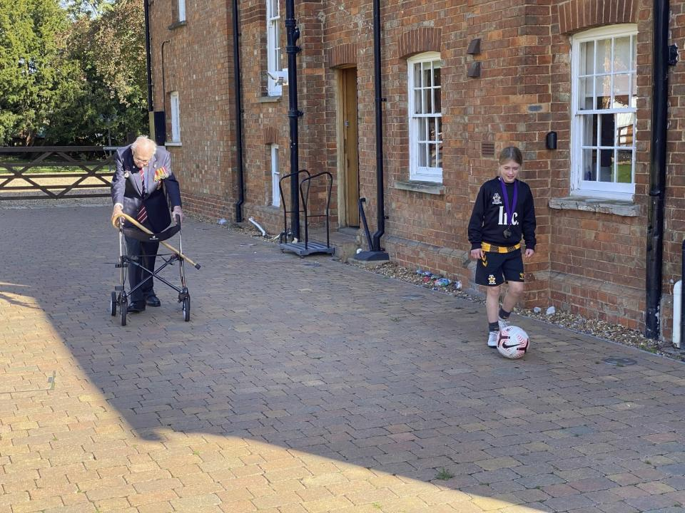 In this Oct. 10, 2020 photo provided by Karl Papworth-Heidel, Captain Tom Moore, left walks with fellow fundraiser Imogen Papworth-Heidel, at his home, in Marston Moretaine, England. The legacy of Capt. Tom Moore, the super fundraiser who died Tuesday, Feb. 2, 2021 of COVID-19, lives on in Imogen Papworth-Heidel — and many others. The 11-year-old soccer player, who dreams of playing for England, watched Capt. Tom pushing his walker up and down his garden to raise money for the National Health Service. So she decided to help by doing something she's good at: keepy uppies — kicking the ball into the air and passing it from one foot to the other without letting it touch the ground. Imogen was able to raise 15,000 pounds ($20,500) for key workers. (Karl Papworth-Heidel via AP)