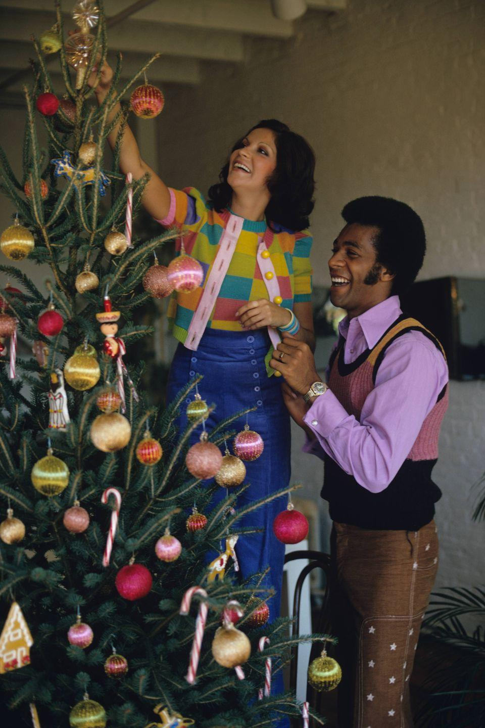<p>Famous songwriter Clifton Davis added a pop of color to his very '70s Christmas look with a color-blocked sweater vest and a lilac button-down.</p>